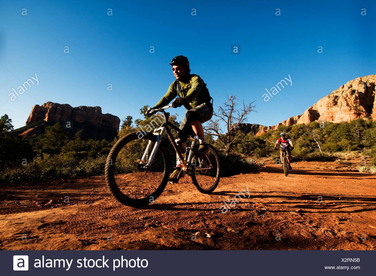 Due media età uomini ride mountain bike attraverso il Red Rock Country di Sedona, AZ. Immagini Stock