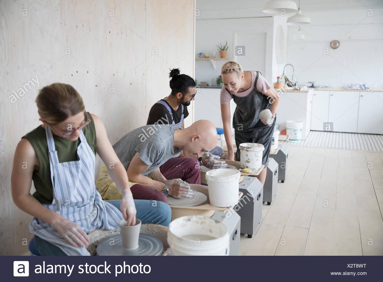 Istruttore ceramiche aiuta gli studenti ad apprendere come utilizzare ruote di ceramiche in art studio Immagini Stock
