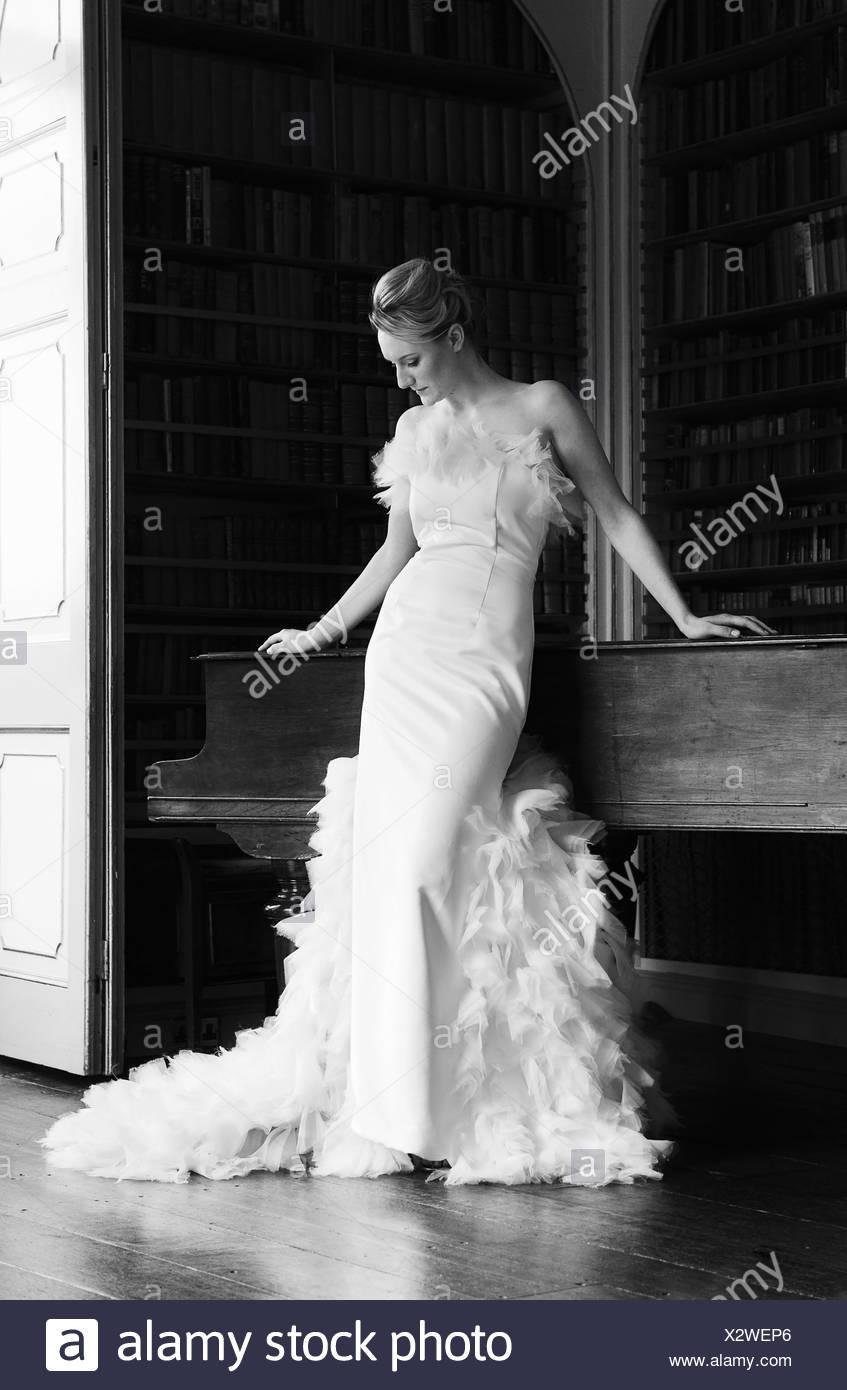 Una donna che indossa un elegante pavimento abito di lunghezza con un completo gonna decorata con piume Inghilterra Immagini Stock