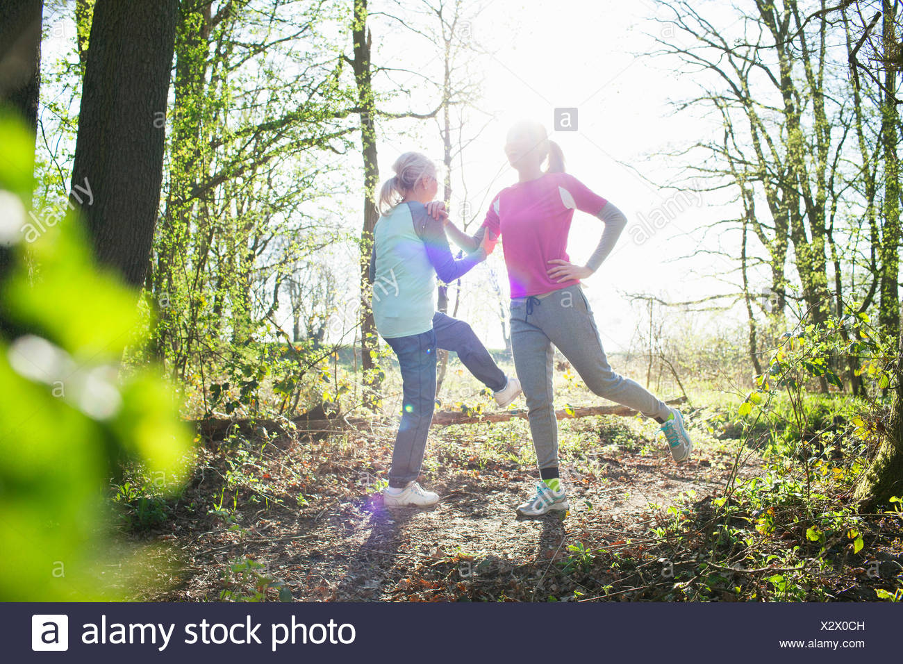 Le donne nella foresta faccia a faccia le gambe sollevate stretching Immagini Stock