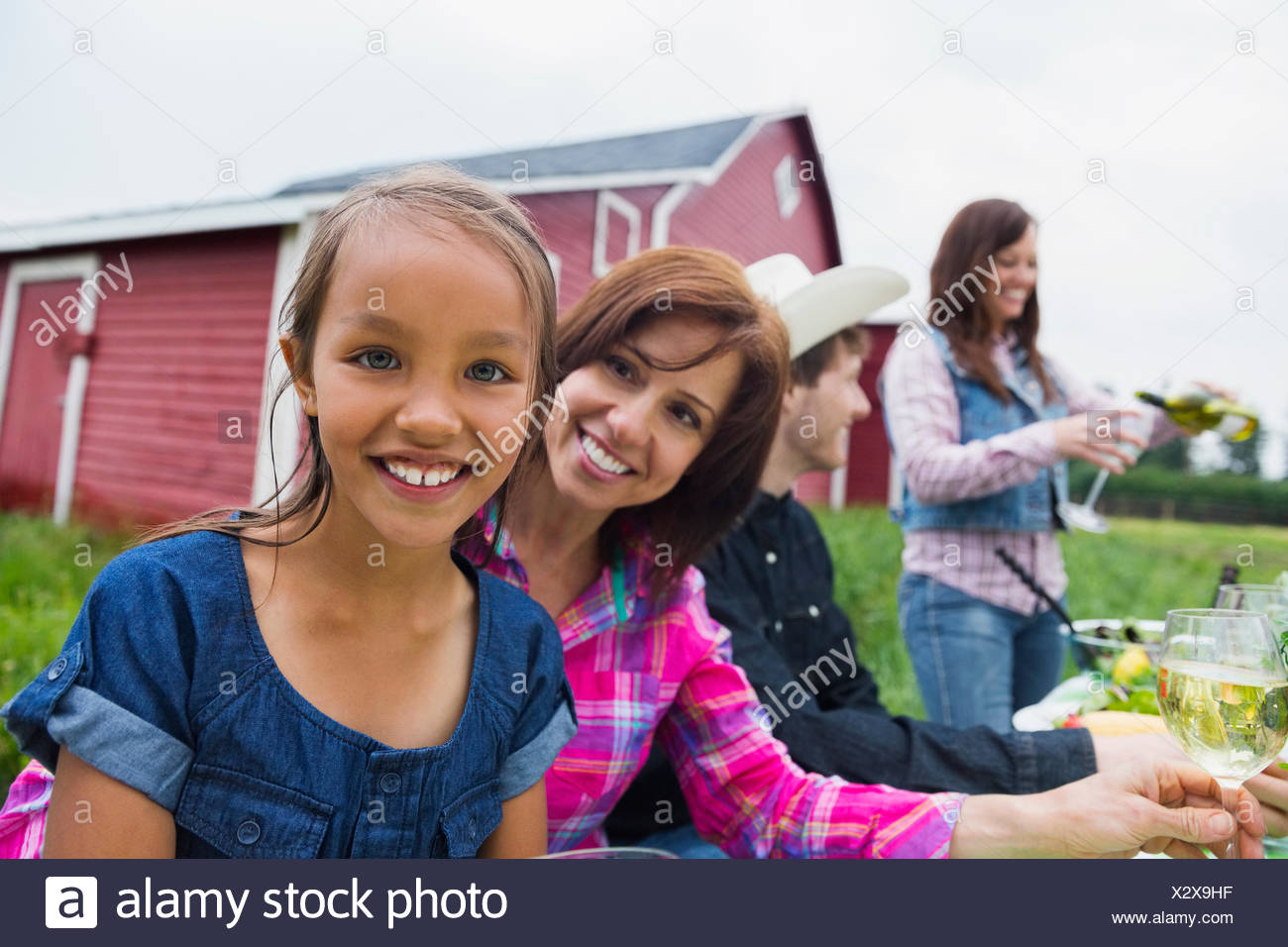 Madre e figlia godendo cena di famiglia al di fuori di un fienile Immagini Stock