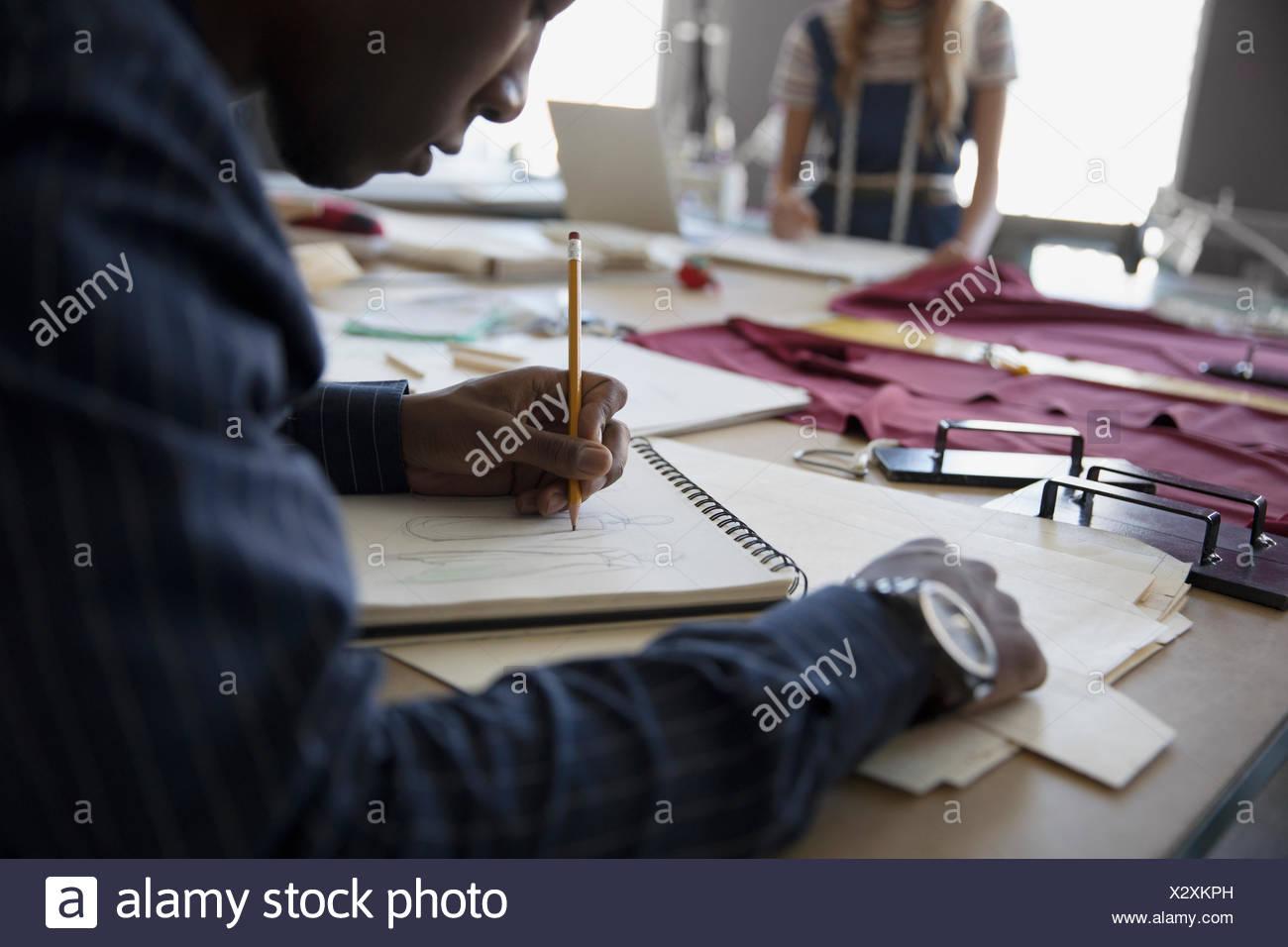 Moda maschile studente di design schizzi al banco di lavoro Immagini Stock