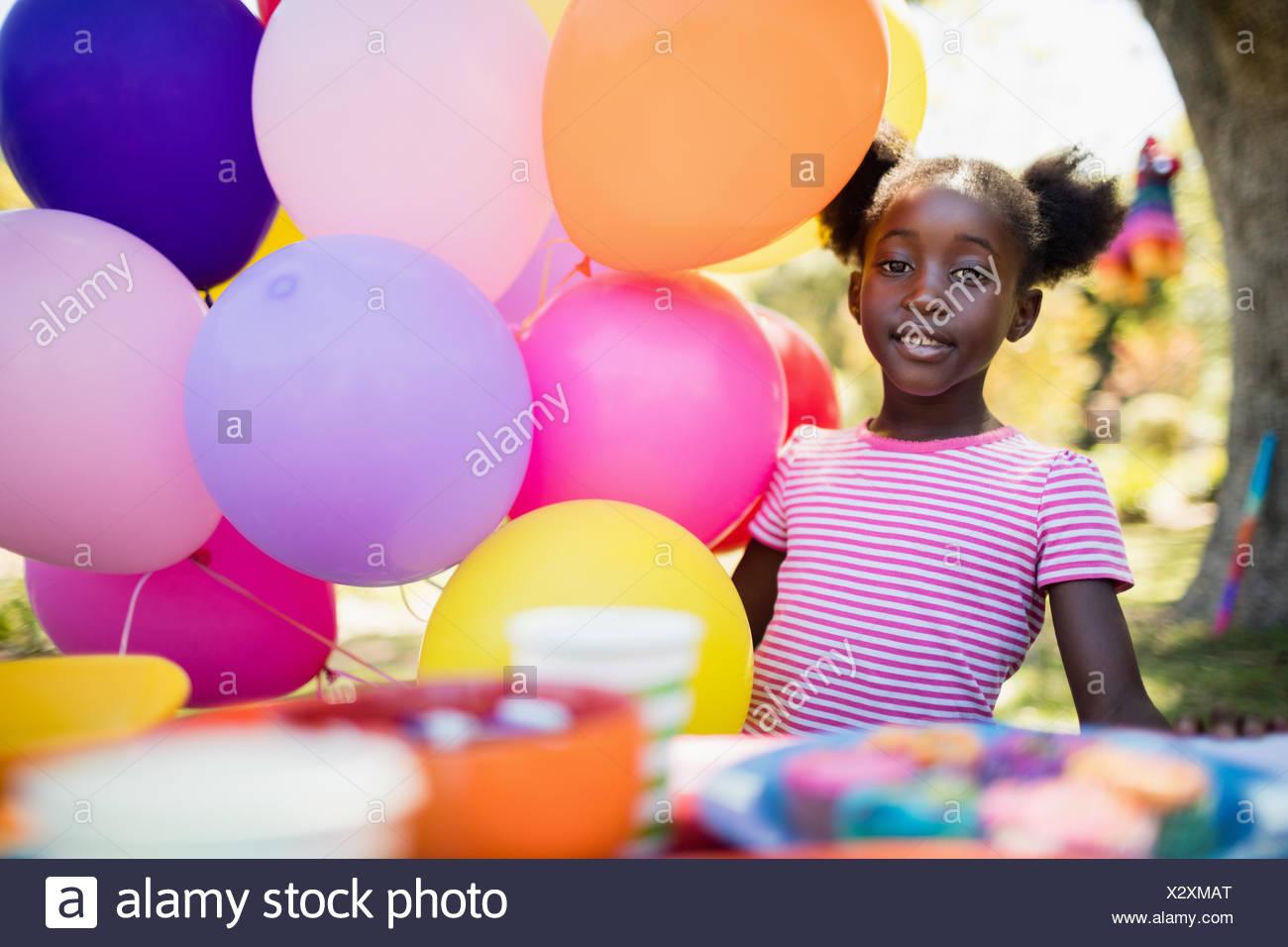 Ragazza carina che pongono accanto al palloncino di una festa di compleanno Immagini Stock
