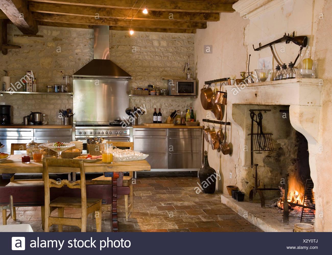 Acceso il fuoco nel camino in cucina di paese con rustici ...