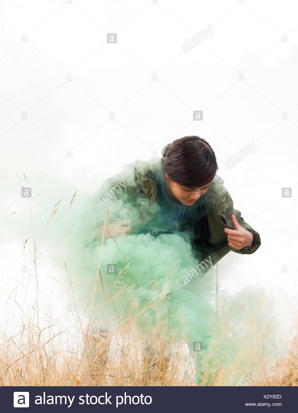 Norvegia, donna in piedi in erba e fumo verde Immagini Stock