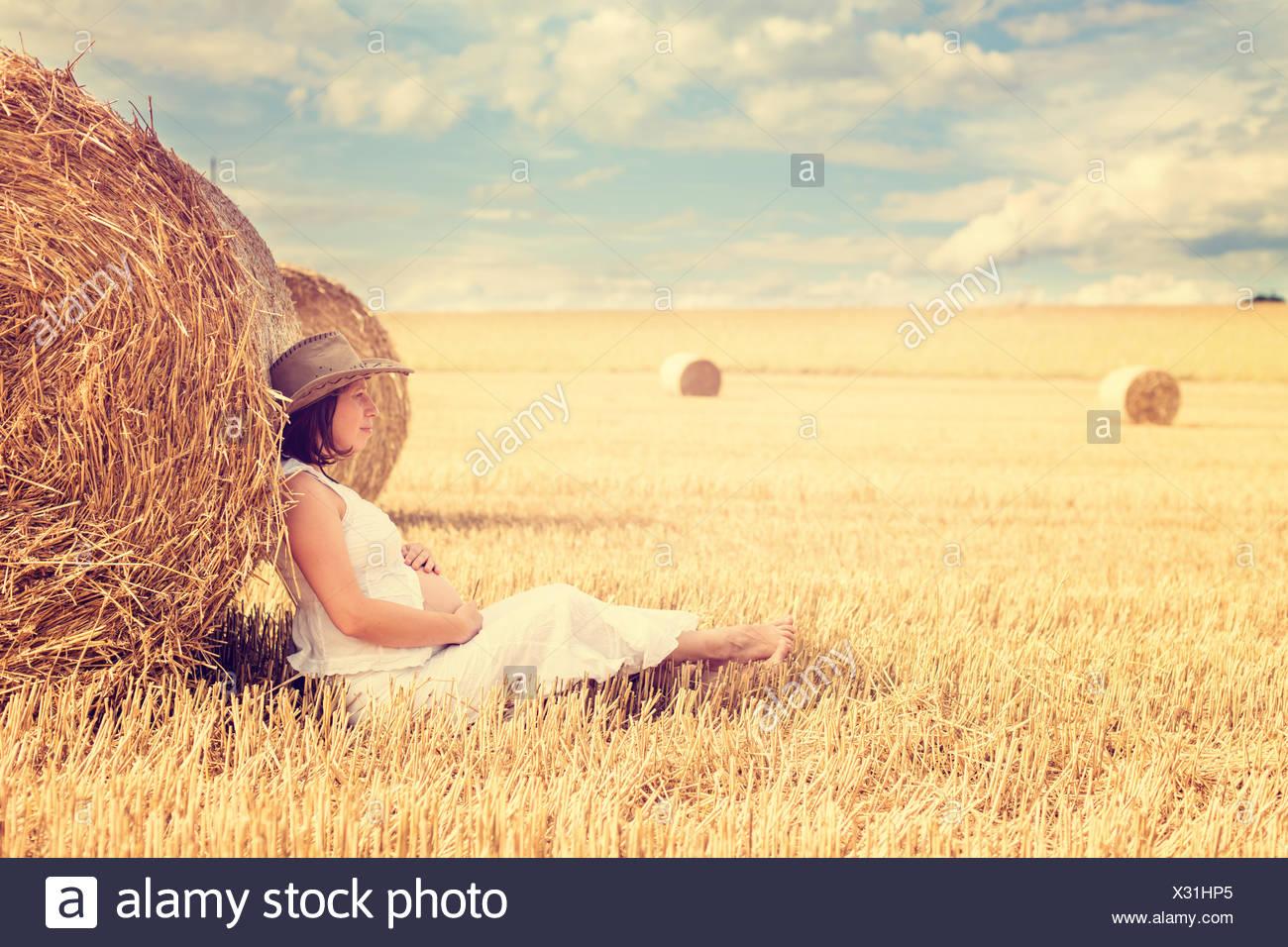 Donna incinta appoggiata contro una balla di fieno in un campo Immagini Stock
