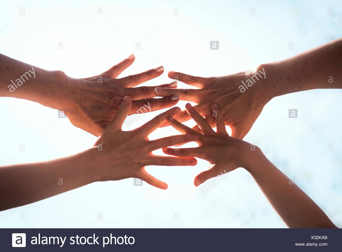 In prossimità di una famiglia le mani insieme contro la luce solare, Baviera, Germania Immagini Stock