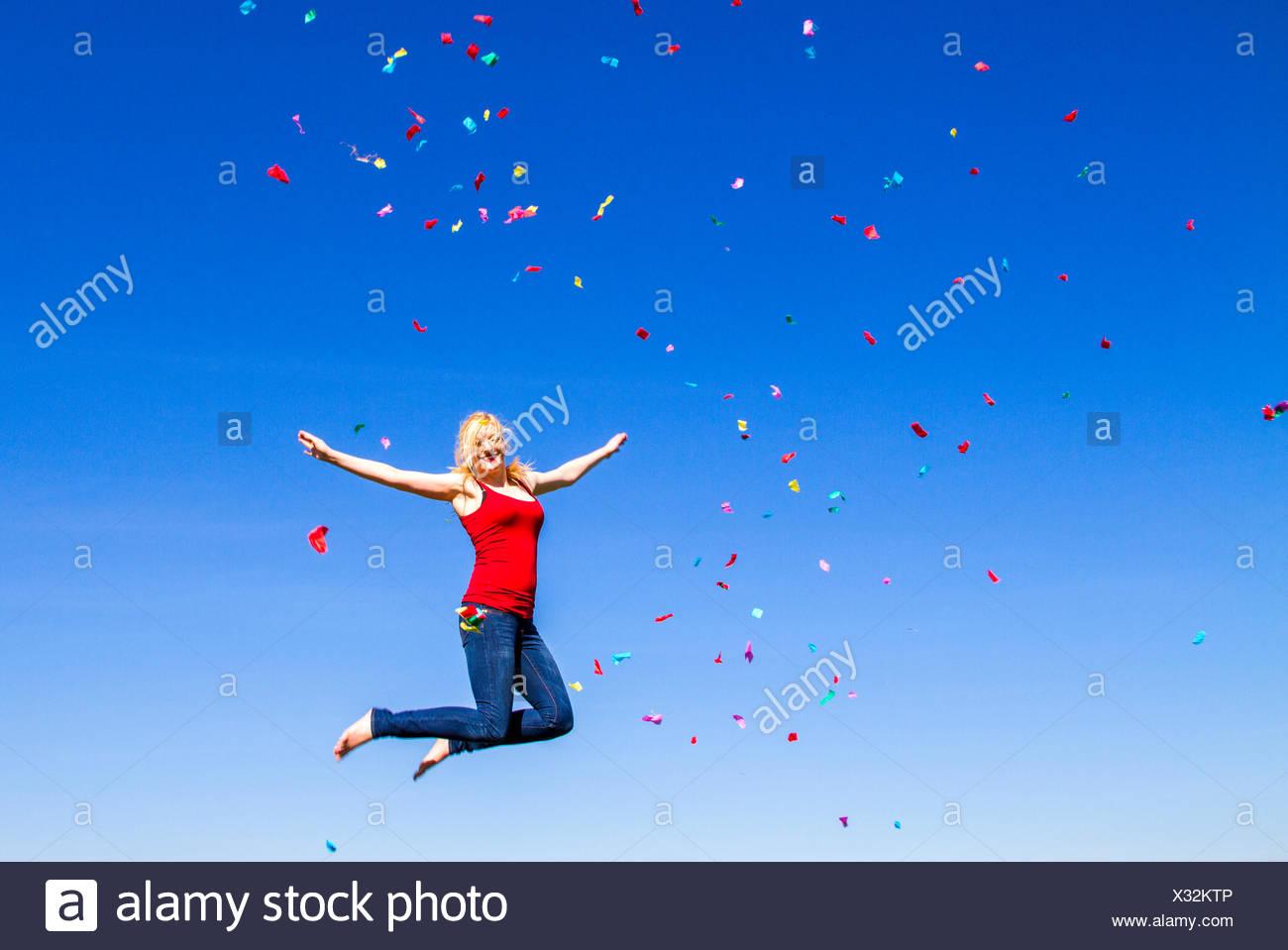 Ritratto di donna bionda jumping con i confetti contro il cielo blu Immagini Stock