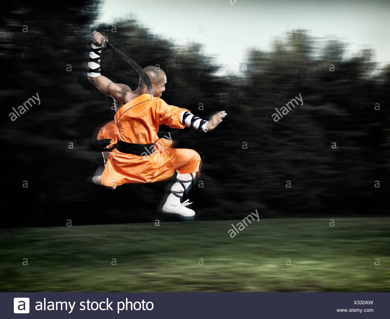 Shaolin monaco guerriero nella metà di salto in aria con un ampio spada Immagini Stock