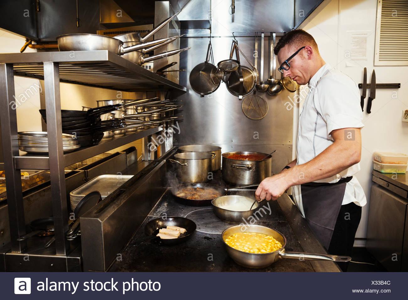 Lo chef cucina in un ristorante di cucina. Immagini Stock
