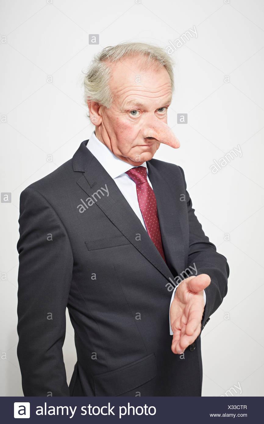 Imprenditore con il naso lungo che offre la mano Immagini Stock