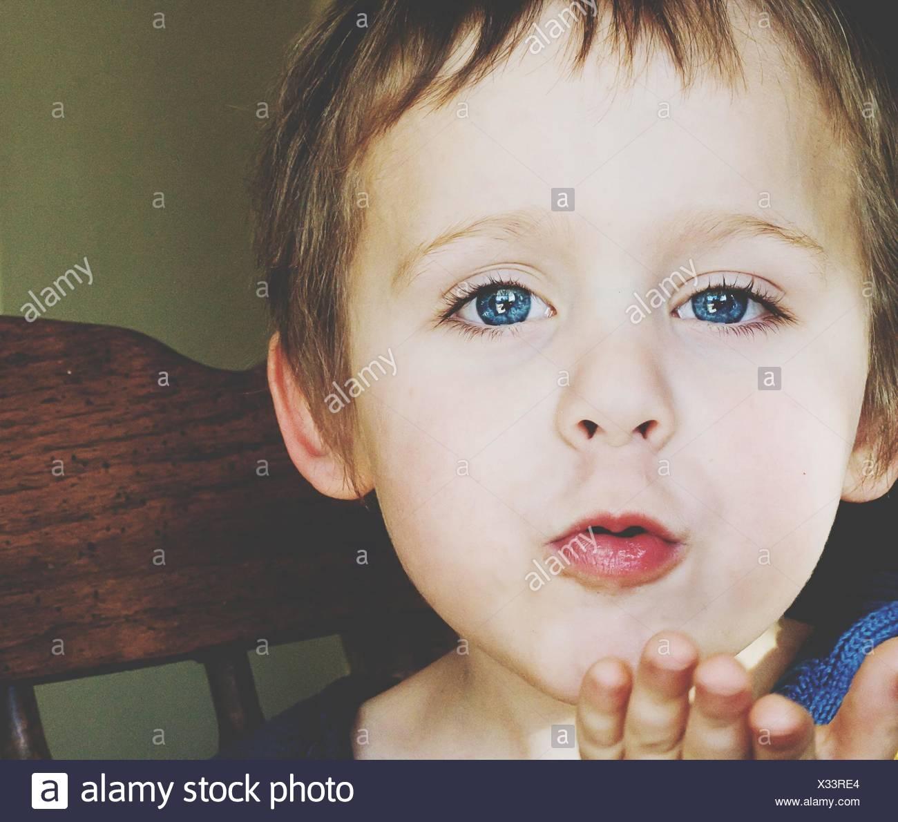 Ritratto di Carino Blue Eyed Boy soffia un bacio Foto Stock