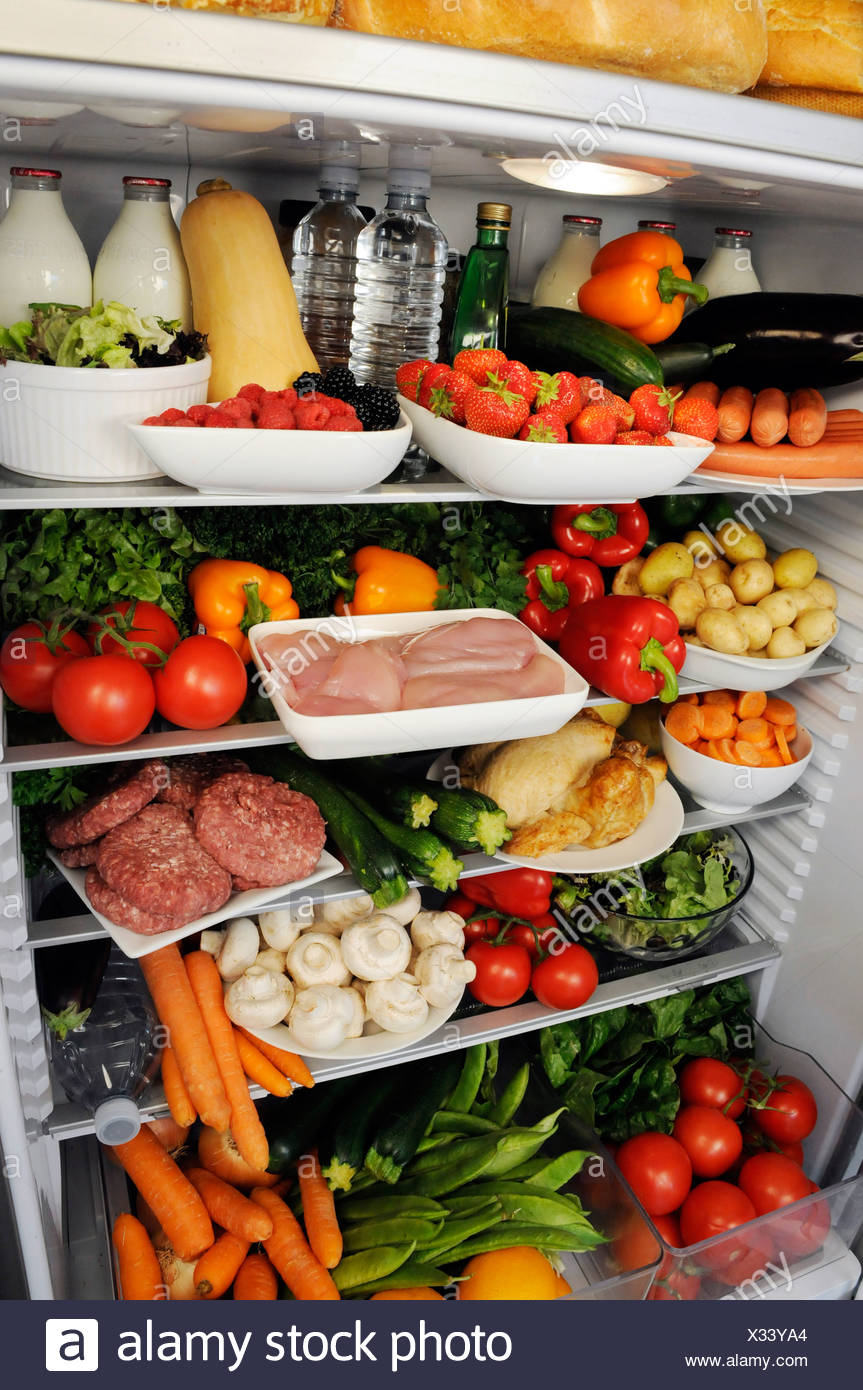 VIEW all'interno del frigorifero con ripiani riempito con cibo fresco Immagini Stock