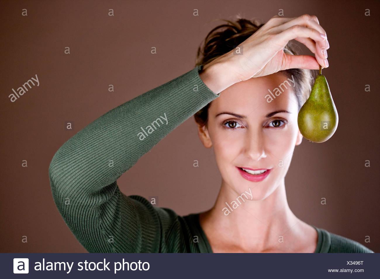 Una metà donna adulta tenendo una pera Immagini Stock