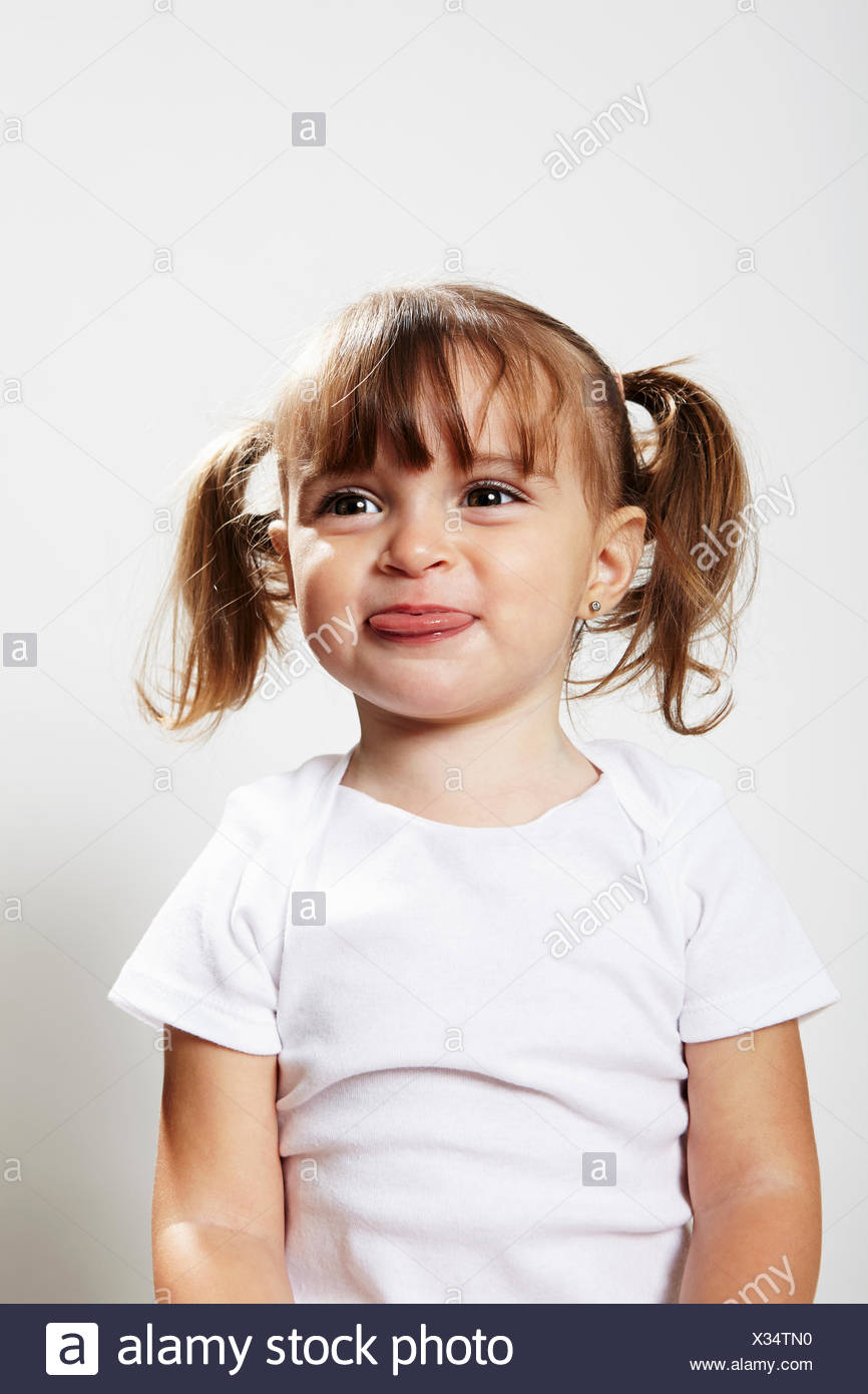 Ritratto di giovane ragazza con pig-tail, rendendo le facce Immagini Stock