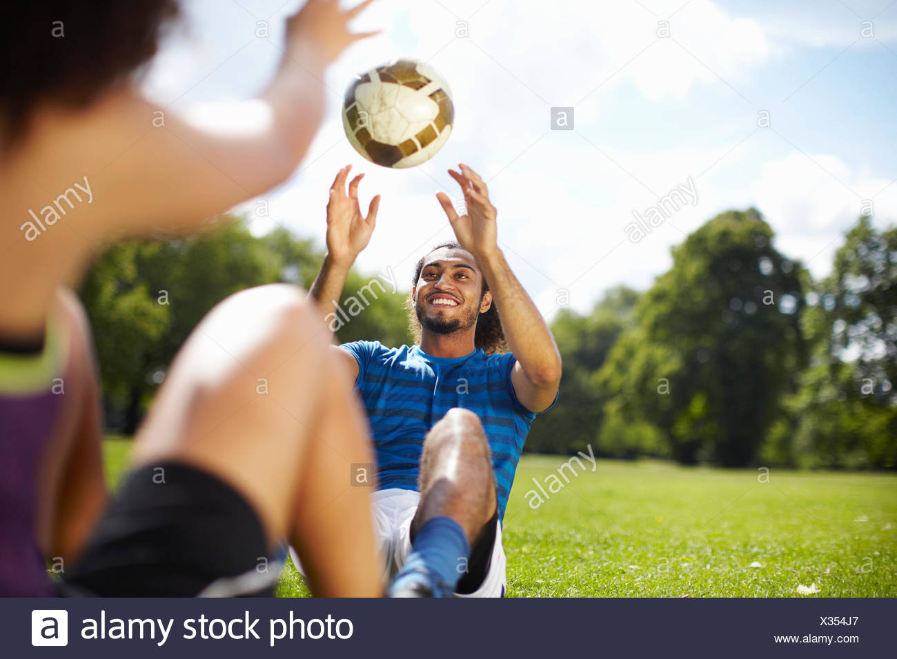 Coppia giovane formazione con pallone da calcio in posizione di parcheggio Immagini Stock