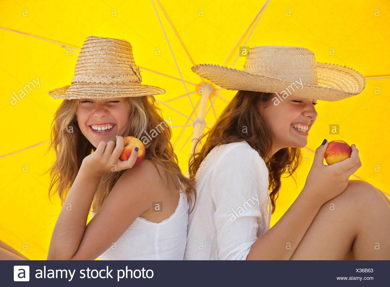 Le belle donne mangiare la frutta in ombra Immagini Stock