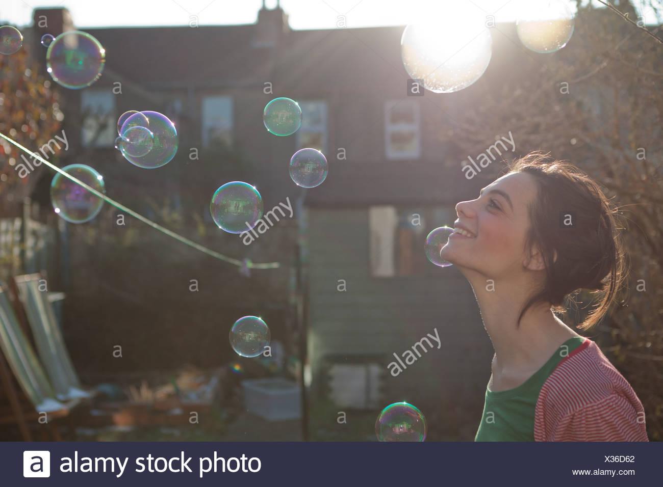 Giovane donna all'aperto con bolle galleggianti in aria Immagini Stock