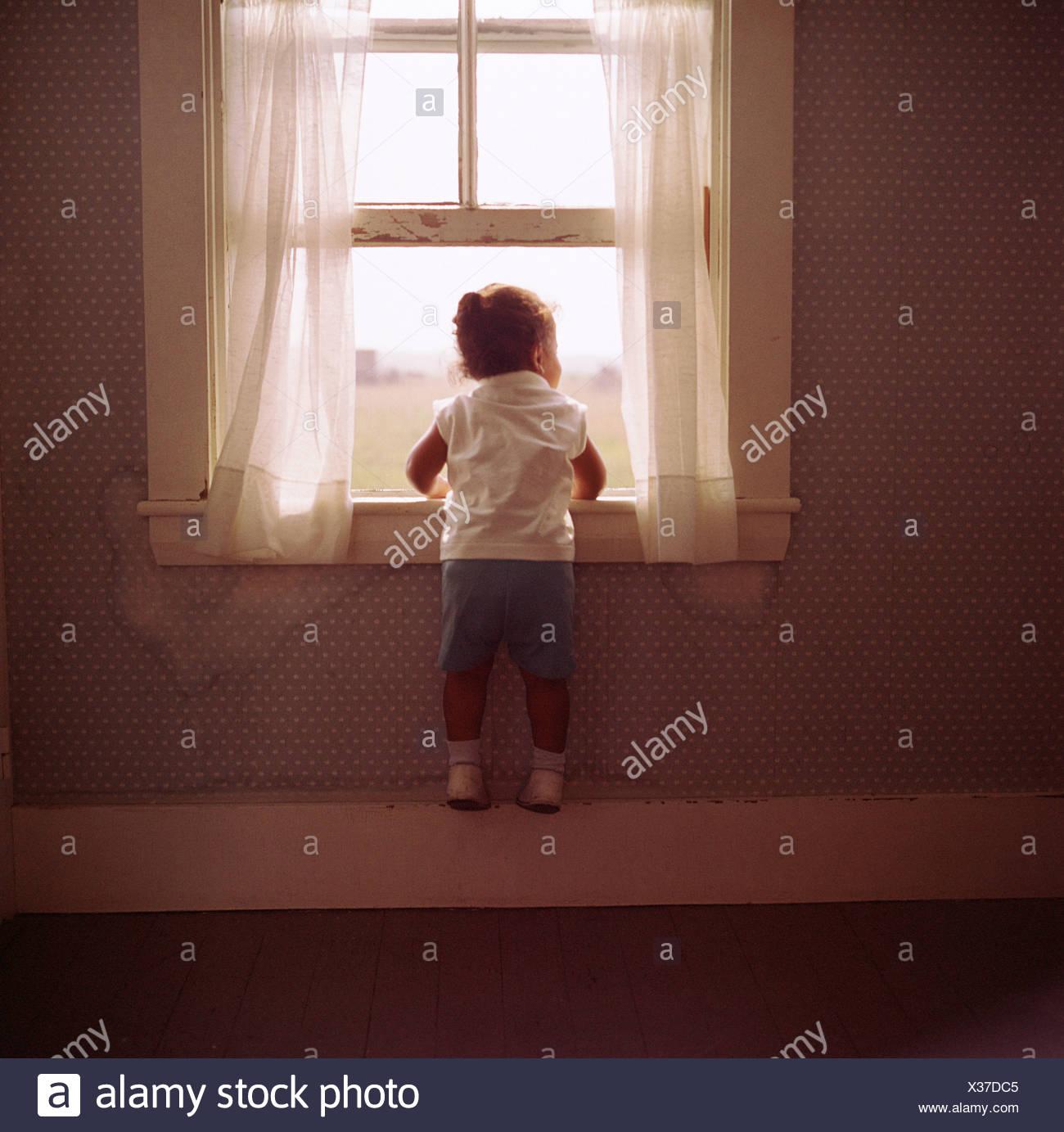 Davanzale Interno Della Finestra bambina guardando fuori dalla finestra appeso al davanzale