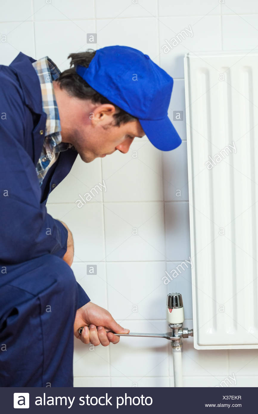 Grave tuttofare in tute blu la riparazione di un radiatore Immagini Stock