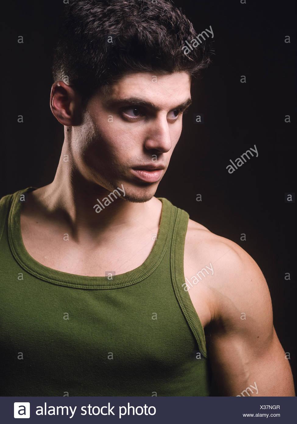 Ritratto di uomo muscolare di fronte a sfondo nero Immagini Stock