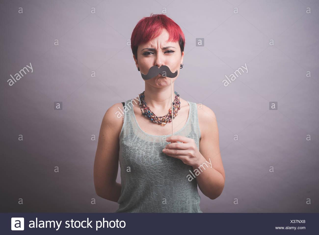 Ritratto in studio di confuse giovane donna regge i baffi nella parte anteriore del viso Immagini Stock