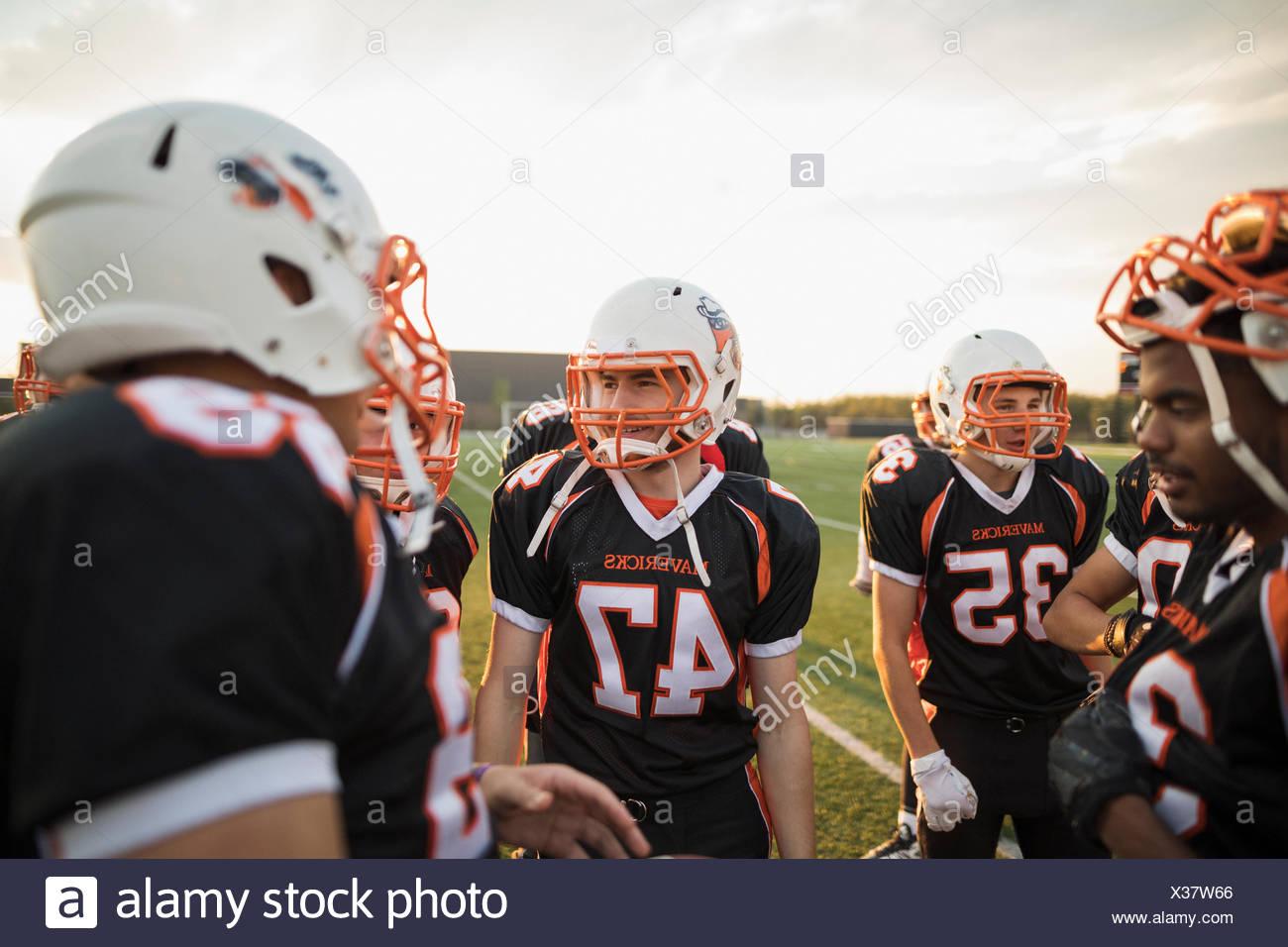 Ragazzo adolescente di alta scuola calcio team parlando a stringersi sul campo di calcio Immagini Stock
