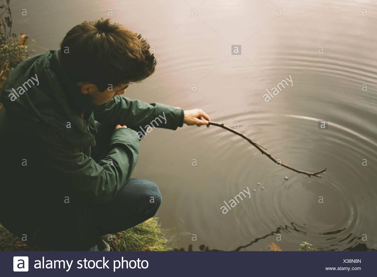 Giovane uomo accovacciato sul lungofiume rendendo le ondulazioni in acqua con ramoscello Immagini Stock