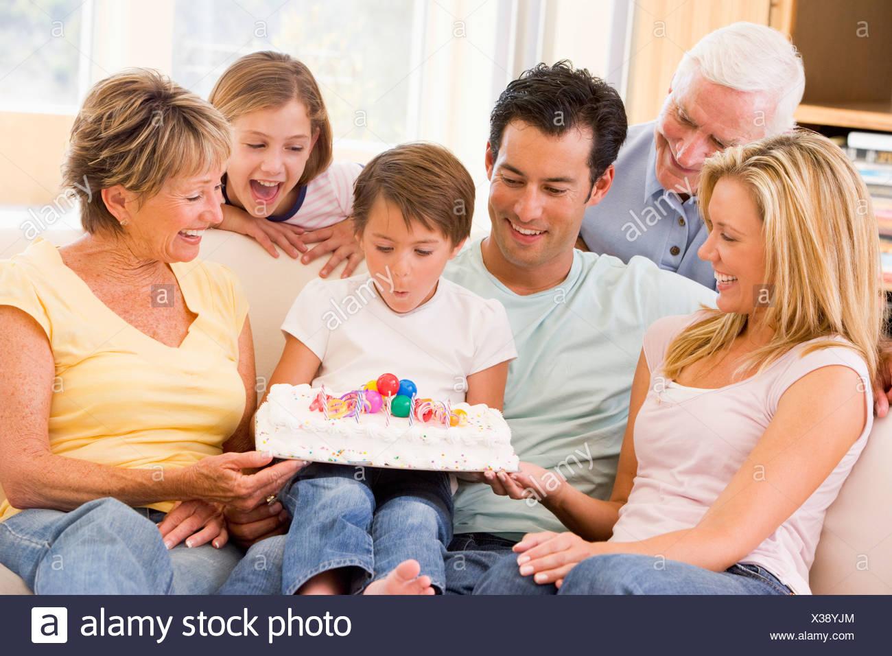 Famiglia in soggiorno sorridente con il giovane ragazzo soffiando le ...