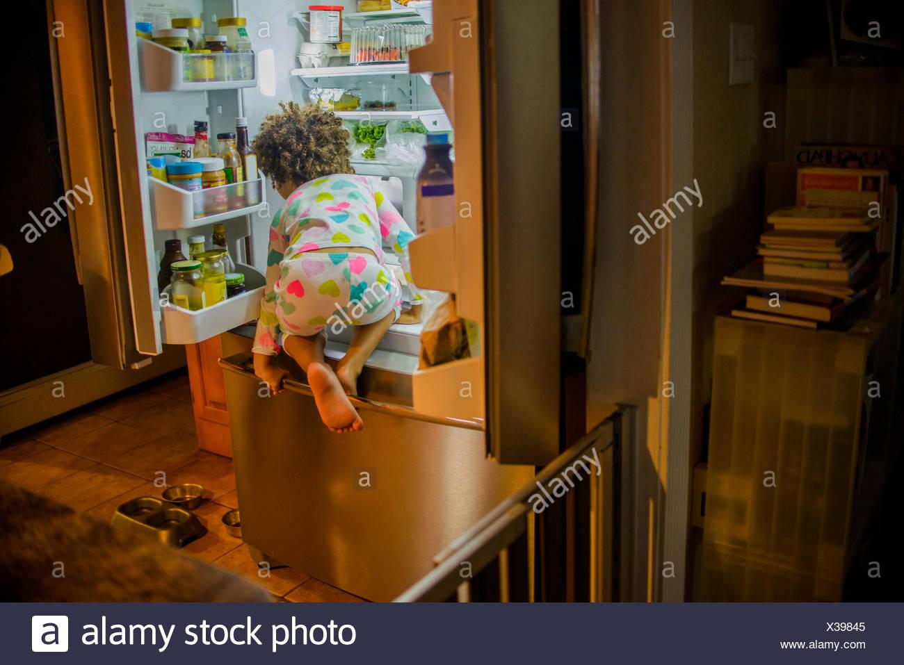 Vista posteriore di una ragazza di intrufolarsi cibo e bevande dal frigorifero durante la notte Immagini Stock