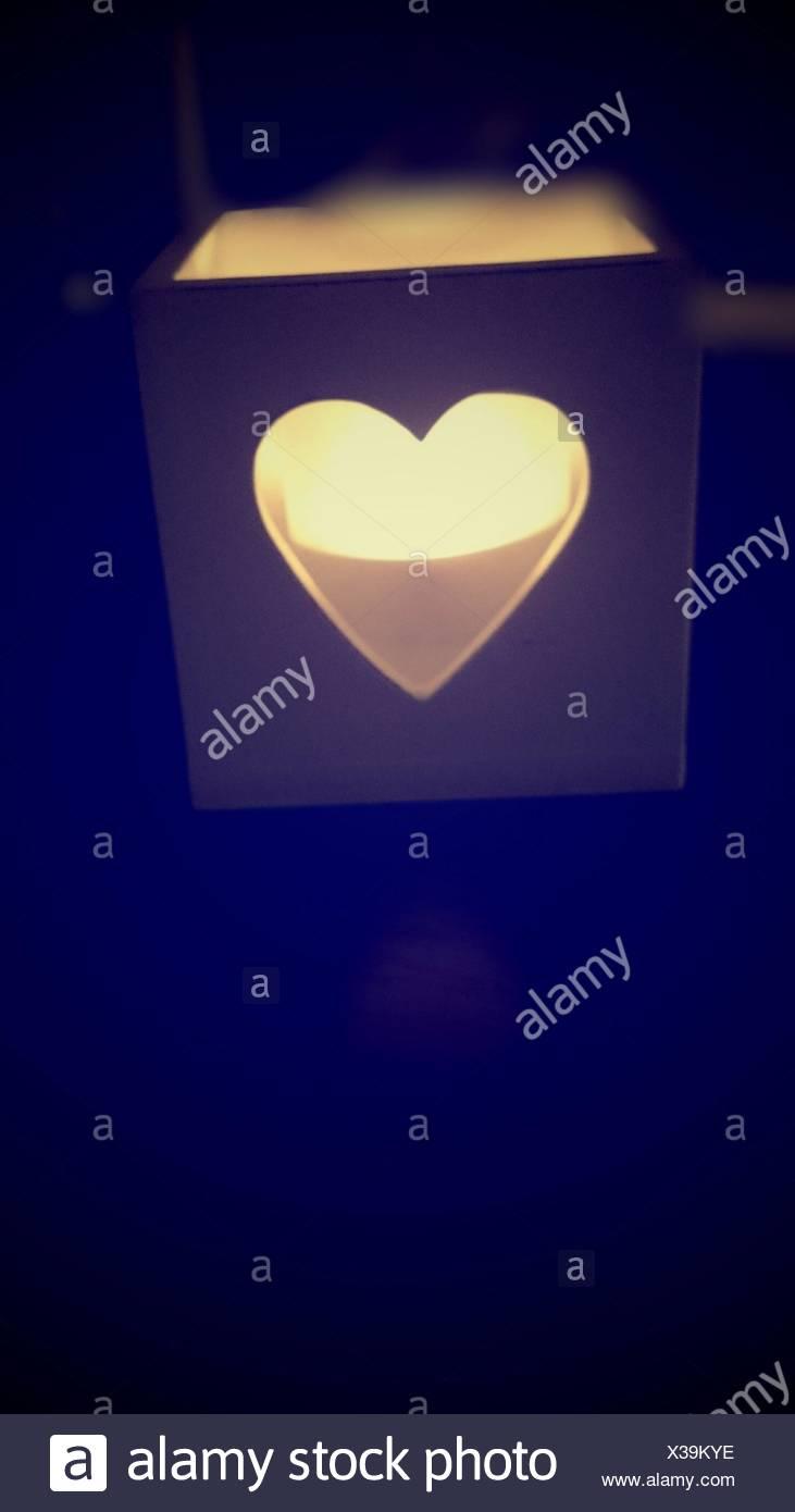 Candela accesa in forma di cuore casella nella camera oscura Immagini Stock