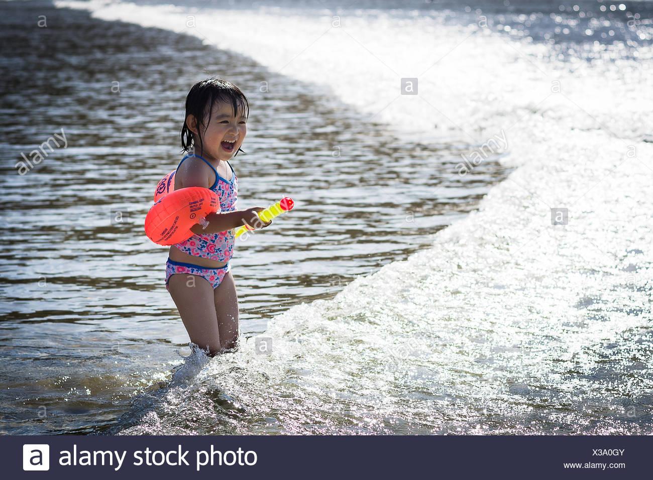 Ragazza indossando costume da bagno e acqua rosso ali giocando in mare increspato Immagini Stock