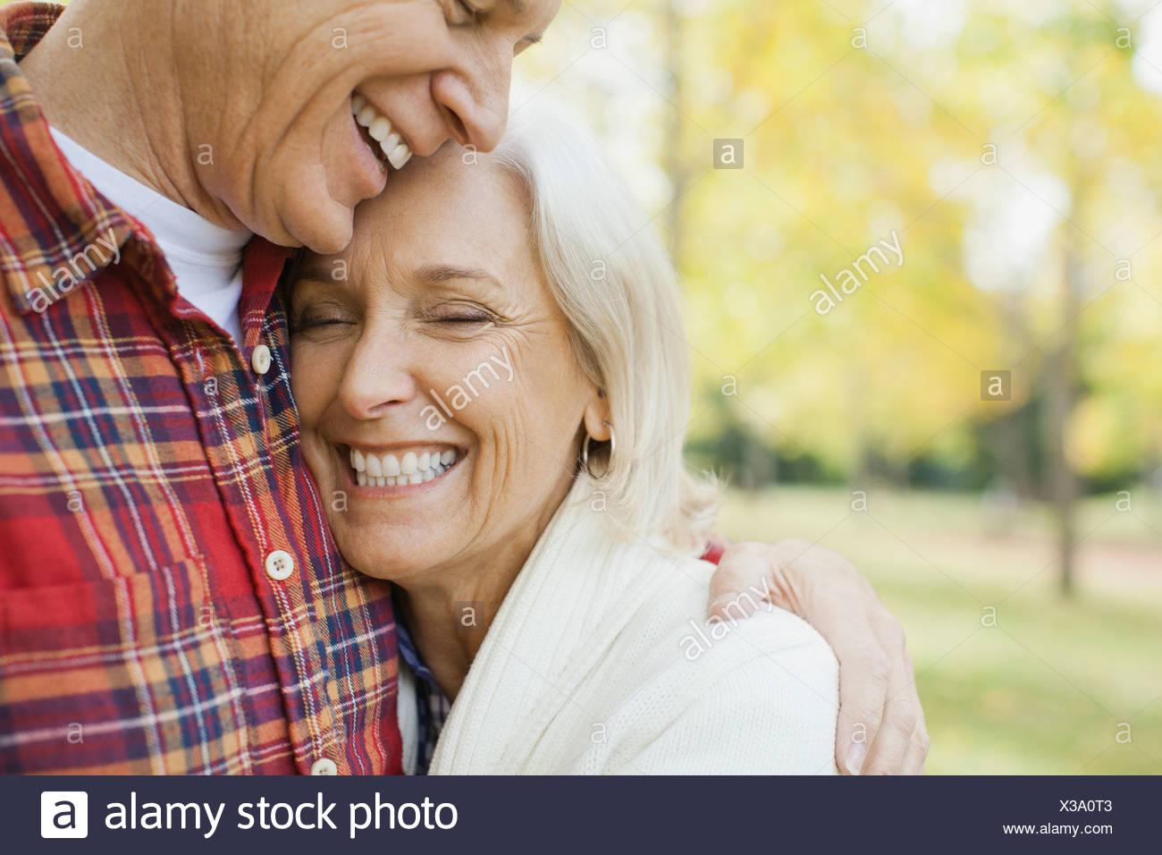 Amare uomo maturo abbracciando la donna in posizione di parcheggio Immagini Stock