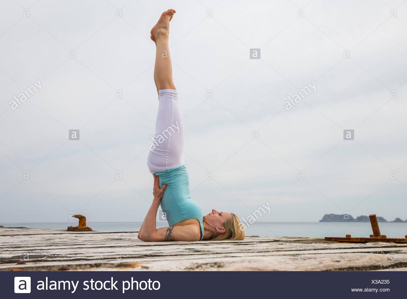 Metà donna adulta con le gambe sollevate a praticare yoga sul mare in legno pier Immagini Stock