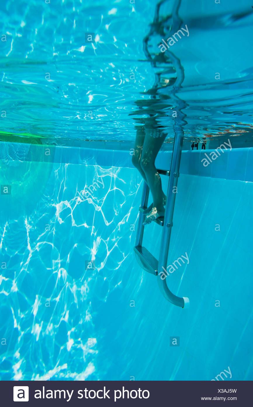 Gambe su scala a gradini in piscina Immagini Stock