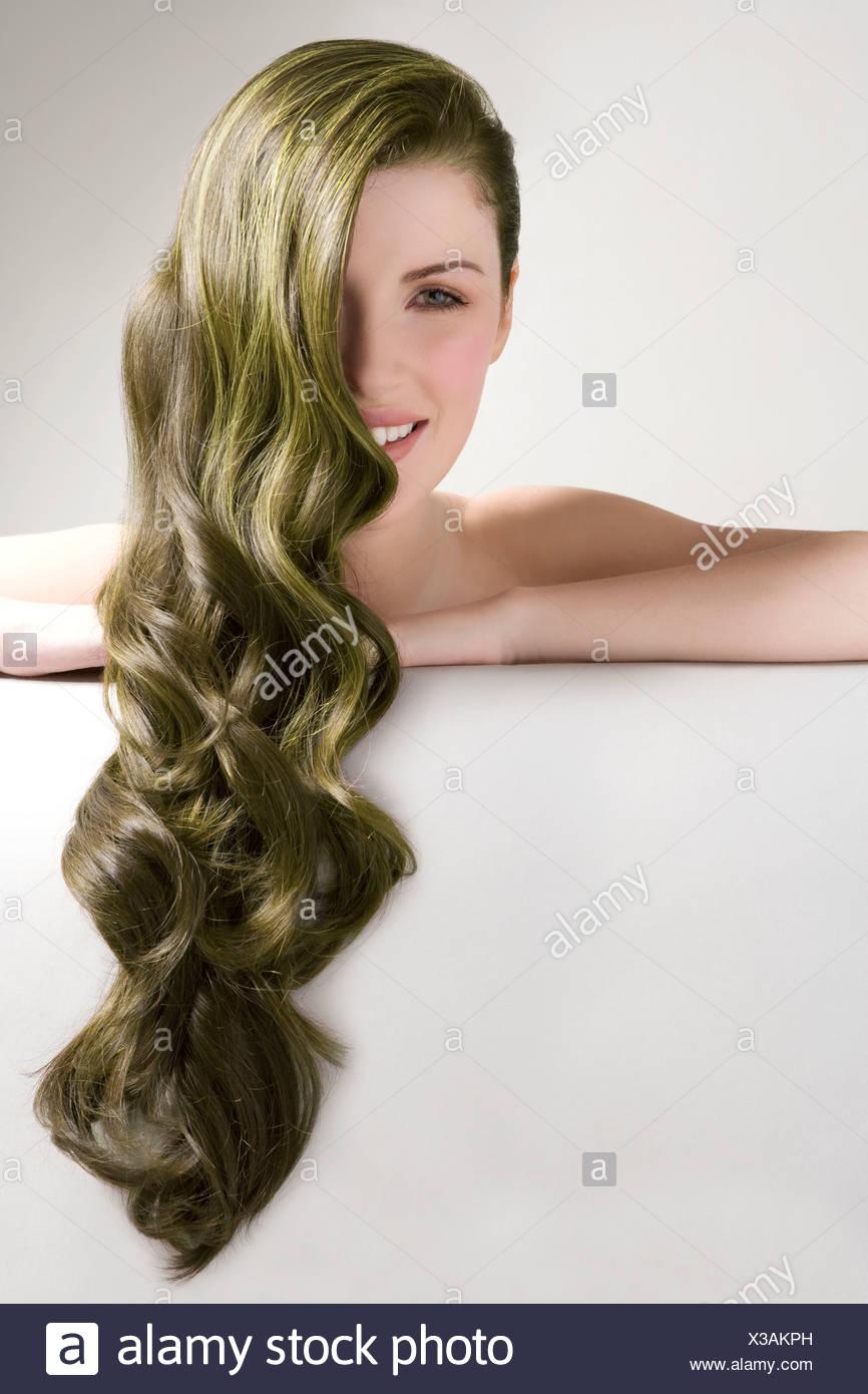Bella donna con verde lungo i capelli tinti contro uno sfondo grigio Immagini Stock
