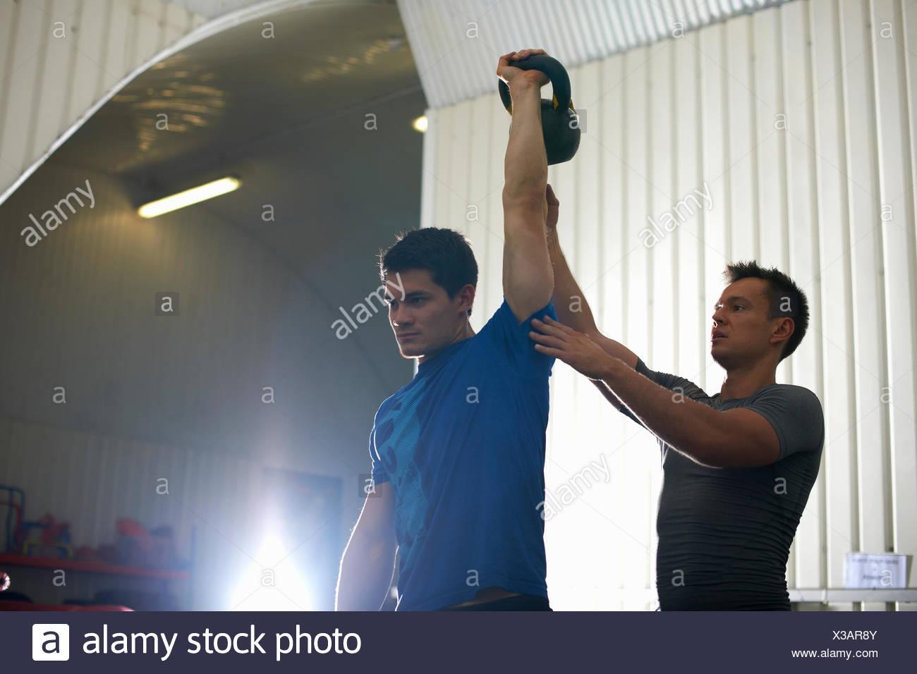 Trainer coaching uomo con kettlebell in palestra Immagini Stock