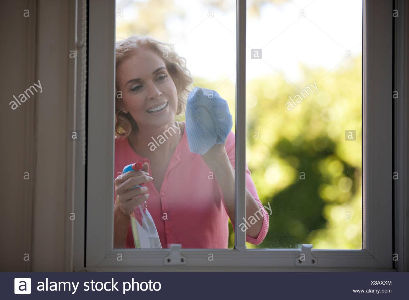 Una donna matura la pulizia di vetri di una casa Immagini Stock