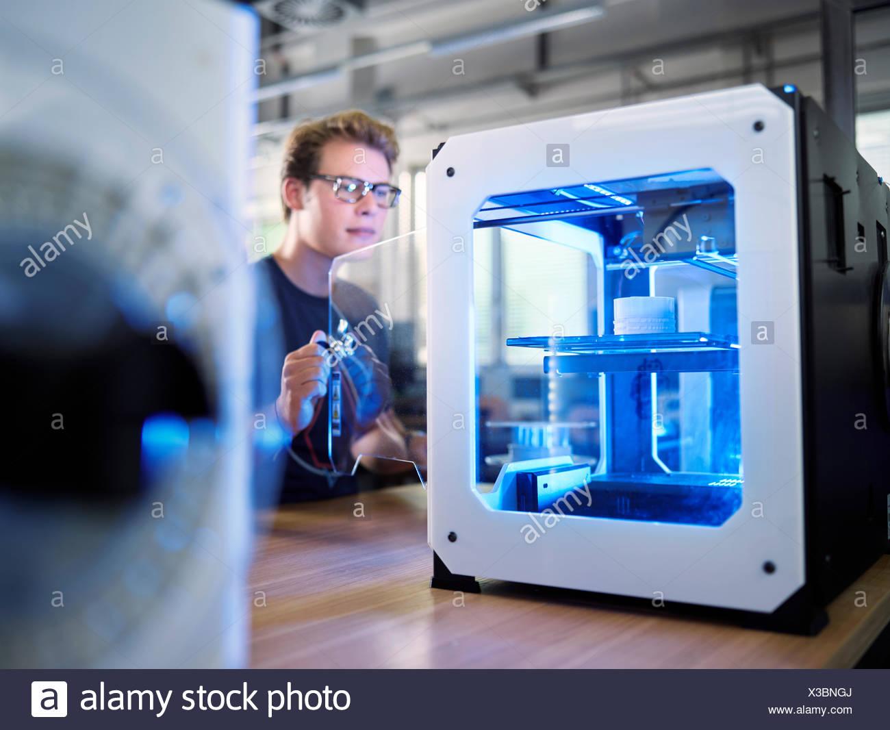 Dipendente, 25-30 anni, apertura stampante 3D nel laboratorio di produzione, FabLab, Wattens, Tirolo, Austria Immagini Stock