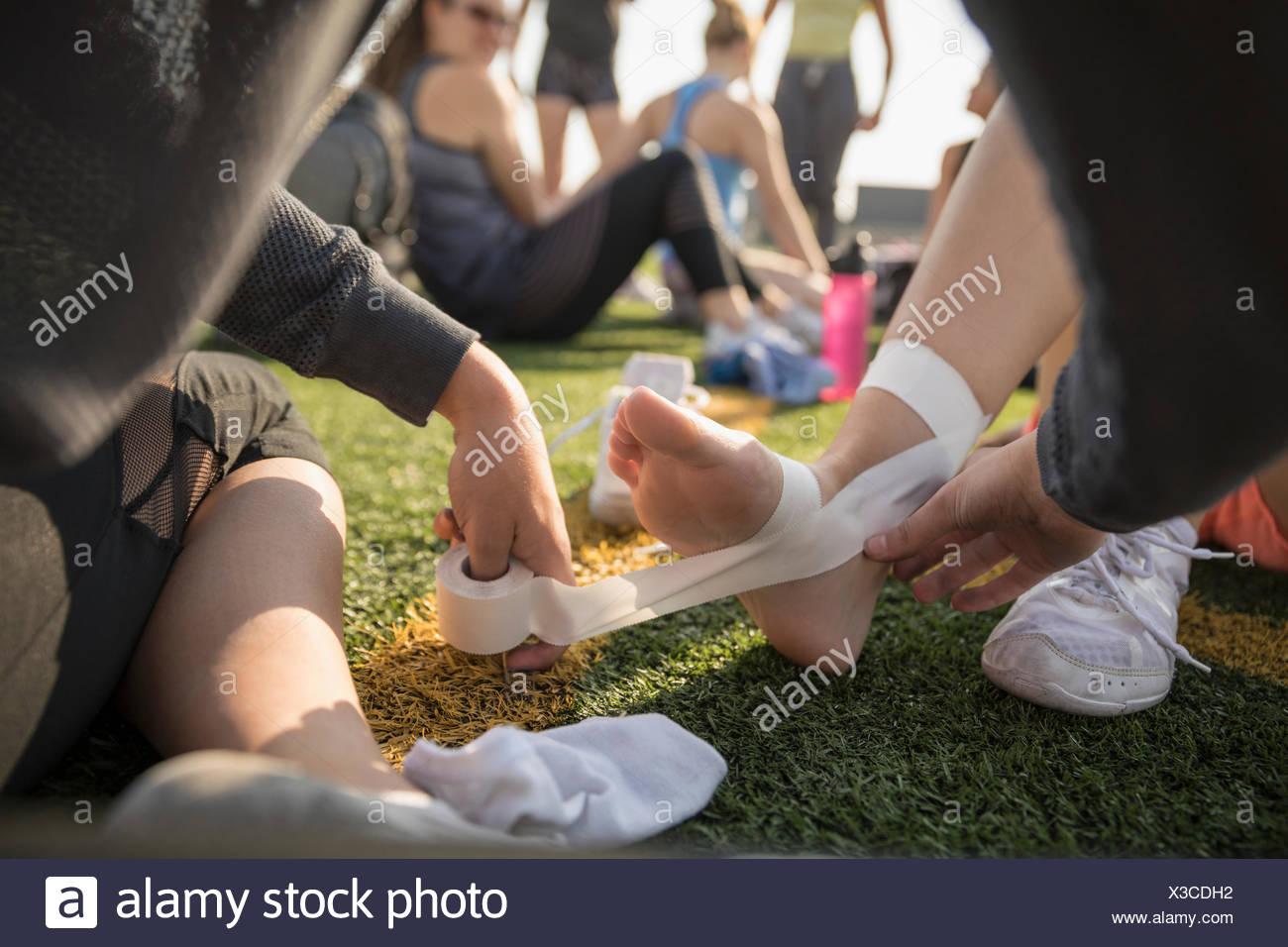 Ragazza adolescente high school cheerleader taping piedi e caviglie con nastro Immagini Stock