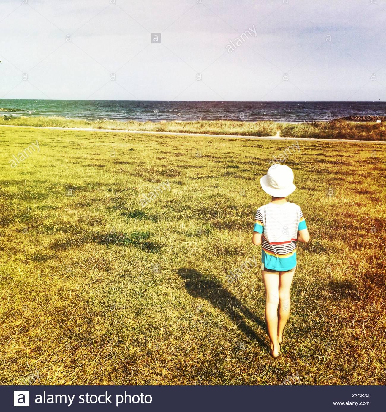 Vista posteriore di un bambino in piedi sull'erba guardando a una vista Immagini Stock