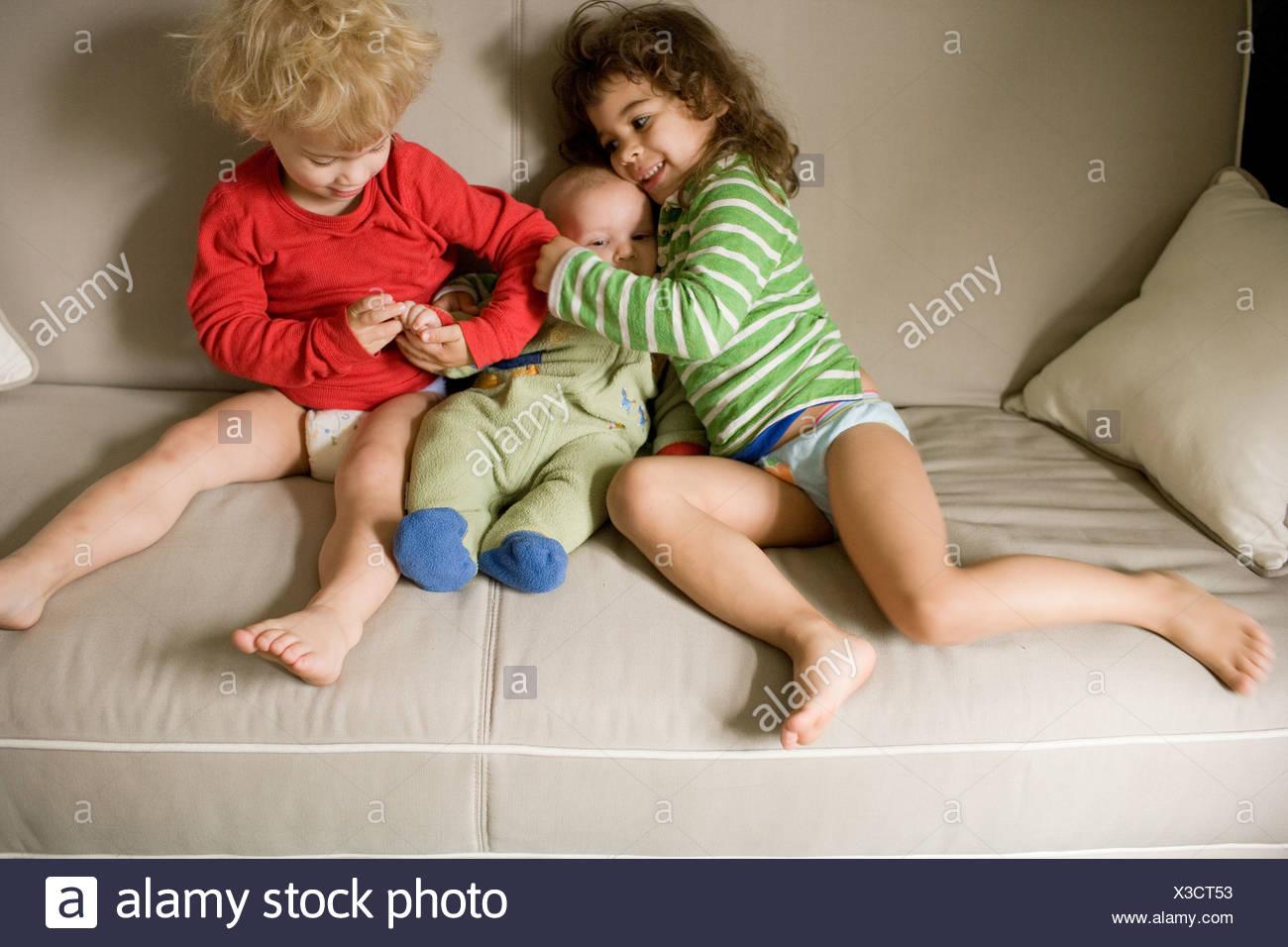 Tre fratelli seduti sul divano Immagini Stock