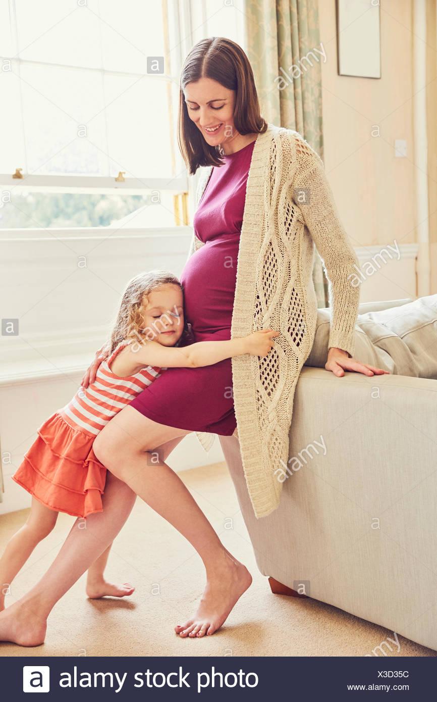Ragazza ascoltando e abbracciando in stato di gravidanza della madre stomaco Immagini Stock