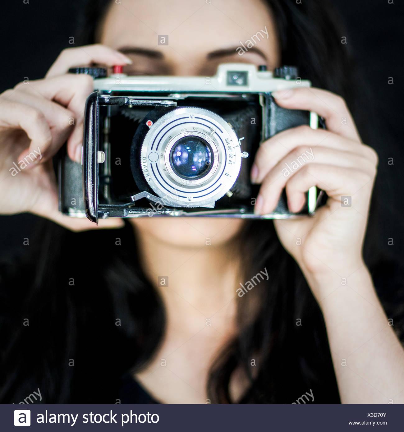 Giovane donna con la vecchia macchina fotografica Immagini Stock