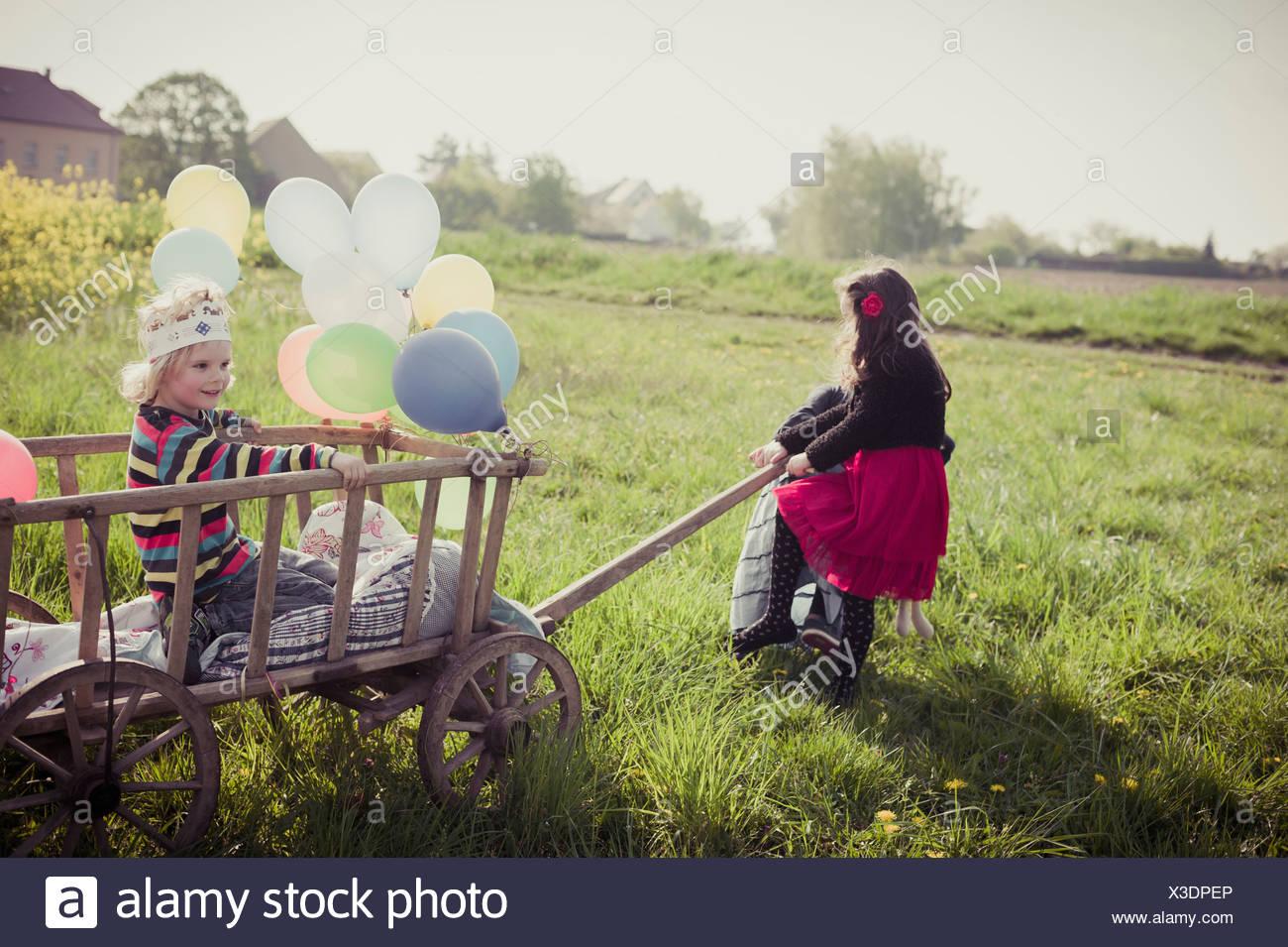 Tre bambini in movimento con carrello in legno e palloncini Immagini Stock