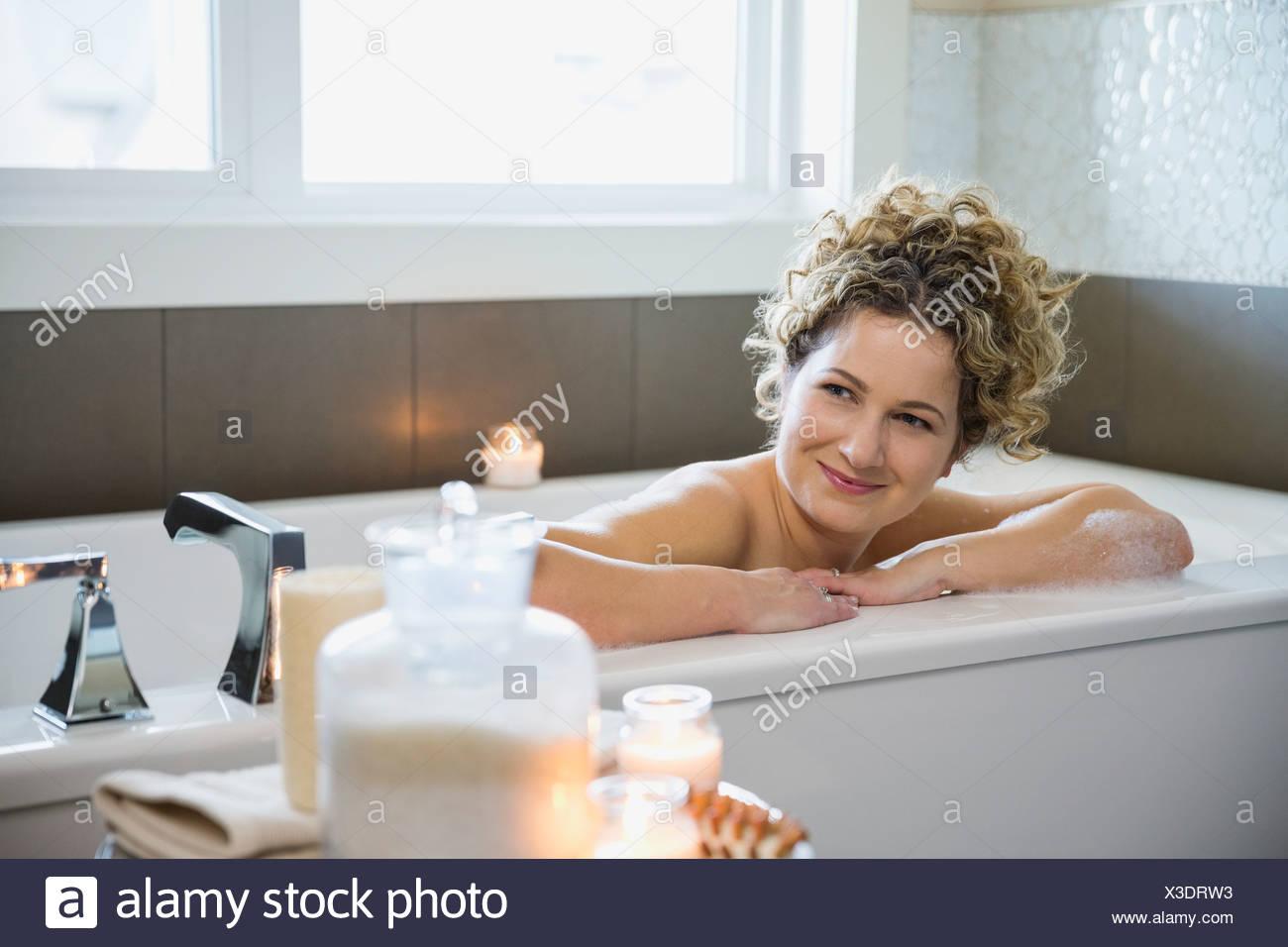 Donna matura che guarda lontano mentre vi rilassate nella vasca da bagno Immagini Stock