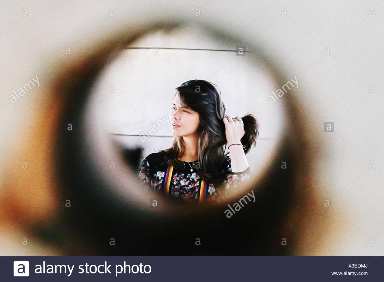 Giovane Donna che mantiene i suoi capelli a casa Immagini Stock