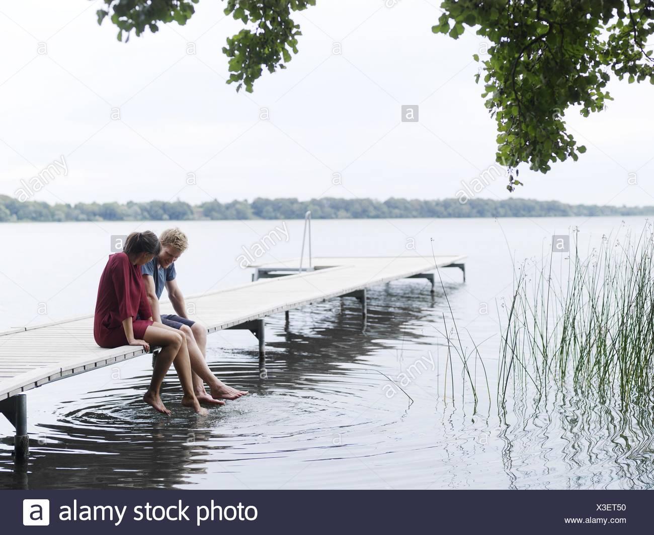 Giovane seduto sul molo a fianco a fianco per immersione dei piedi in acqua, Copenhagen, Danimarca Immagini Stock