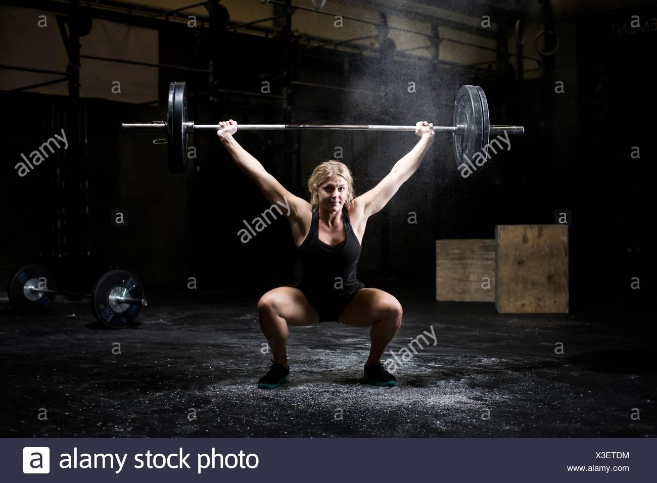 Giovane donna pesi barbell in palestra scuro Immagini Stock