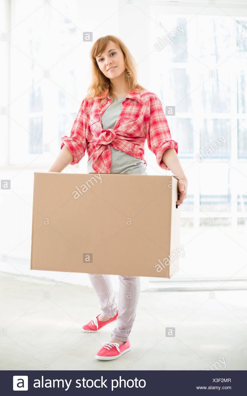 A tutta lunghezza ritratto di donna che porta una scatola di cartone Immagini Stock